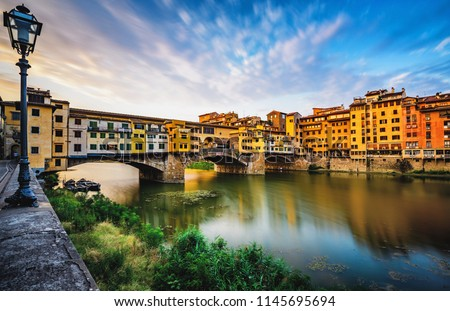 Colorful long exposure of the sunrise at Ponte Vecchio bridge over the river Arno in Florence Italy