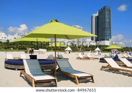 Colorful lounge chairs and umbrellas in popular South Beach in Miami.