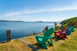 Colorful lounge chairs with a view of beautiful scenic panorama  (Cape Breton Highlands National Park, Canada)