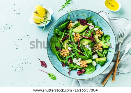 Colorful lunch - spring salad. Fresh leaves, avocado, walnuts, feta cheese and olive oil in a blue bowl. Meal captured from above (top view, flat lay) on a pastel stone background. Free copy space. Foto d'archivio ©