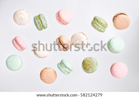 Colorful macarons cake, top view flat lay, fly falling sweet macaroon on color white isolated background. Minimal concepts falling macaroons pattern above, food natural background