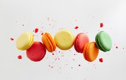 Colorful macarons cakes. Small French cakes. Sweet and colorful french macaroons falling or flying in motion.