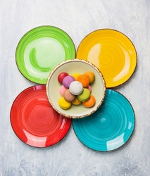 Colorful macarons on color plate, top view, copy space
