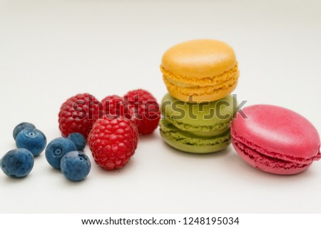 Colorful macaroon coolies with raspberry and blueberry berries on white background