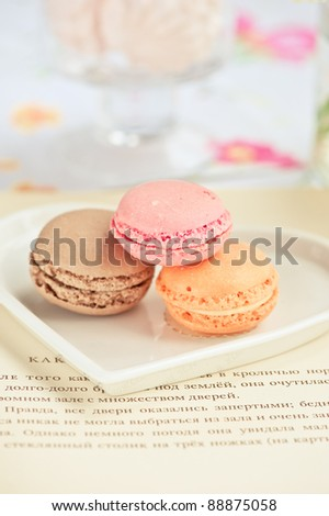 colorful macaroons on a plate and an open book