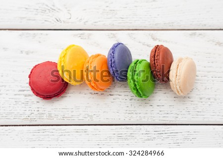 colorful macaroons on white wooden background - Shutterstock ID 324284966