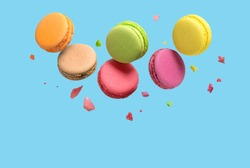 Colorful macaroons or macarons falling or flying over blue background. Copy space.