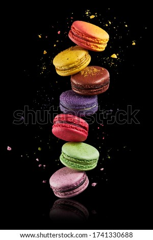 Colorful macaroons stack on black background with crumbs. Food levitation, flying