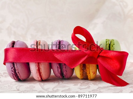 Colorful  macaroons with red ribbon bow  on  a  beige  napkin background