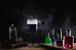 Colorful magic potions in glass bottles on black background. Medieval alchemist laboratory with various kind of flasks and old books.