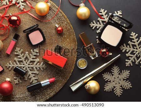 Colorful makeup cosmetic with Christmas decoration on golden beaded mat