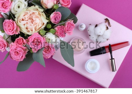 Colorful makeup products on pink background with flowers #391467817