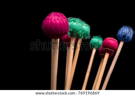 Colorful mallets on a black background. #769196869