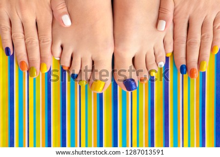 Colorful manicure on short nails and pedicure on striped background. Striped design. #1287013591