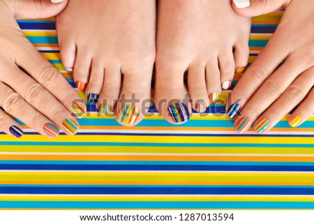 Colorful manicure on short nails and pedicure on striped background. Striped design. #1287013594