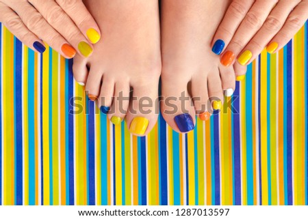 Colorful manicure on short nails and pedicure on striped background. Striped design. #1287013597