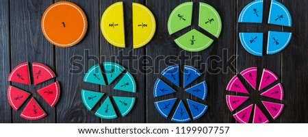 colorful math fractions and apples as a sample on brown wooden background or table. interesting math for kids. Education, back to school concept. Geometry and mathematics materials.