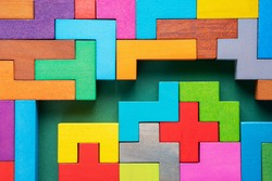 Colorful maze on green background. The concept of a business strategy, analytics, search for solutions, the search output. Labyrinth of colorful wooden blocks, flat lay.