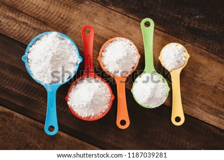 colorful measuring cups with flour on wooden table. Concept of cooking and kitchen tools
