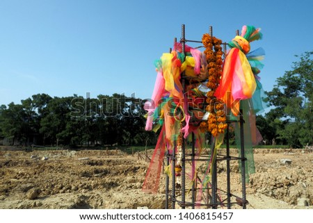 Colorful mesh & garlands are used for a ceremony at a new construction site. Thais wish & pray for prosperity, good luck through this religious rituals as a cultural belief.  Many dug holes on ground.