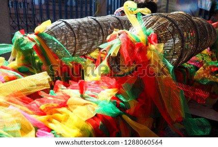 colorful mesh material usually found in Thai temples, superstition as ancient belief and tradition.  Thais wish & pray for prosperity, good luck through religious rituals, ceremony.  a Thai culture