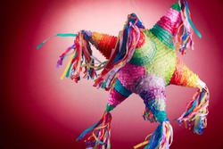 Colorful mexican pinata used in birthdays on red background