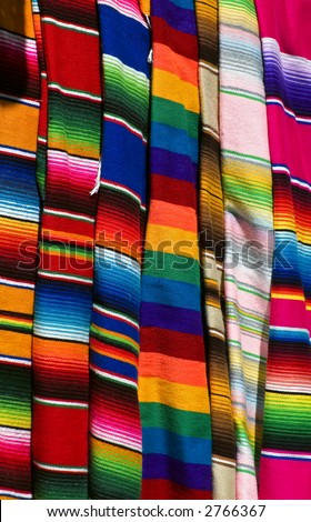 Colorful Mexican serapes hang in row