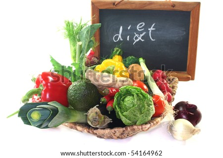 Colorful mix of many different fresh vegetables in a basket with a board