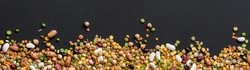 Colorful mixed cereals and legumes: rice,peas, lentils, beans, chickpea on black background. Top view. Empty space for text.