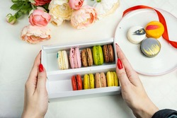 colorful modern macaroons in gift box in female woman hands and on plate for celebration romantic party birthday, pion flowers, satin ribbon, many different types flavors of macaron. Gentle flat lay