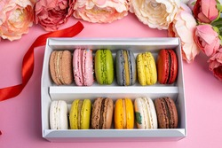 colorful modern macaroons in gift box on pink celebration romantic party birthday, pion flowers, satin ribbon, many different types flavors of macaron. Gentle flat lay top view