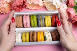 colorful modern macaroons in gift box on pink in female hands celebration romantic party birthday, pion flowers, satin ribbon, many different types flavors of macaron. Gentle flat lay top view