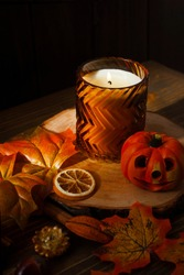 Colorful moody view of autumnal home decor with candle, leaves and dried fruits on rustic wooden surface.