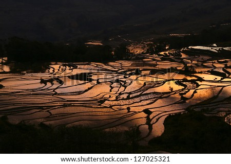 colorful morning skies is seen on the reflection over the terraced rice fields on Yuan Yang County, China.