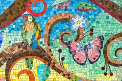 Colorful mosaic artwork close-up. Ceramic tiles pattern with flower, bird and butterfly