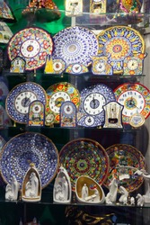 Colorful mosaic ceramic plates, mugs, clocks on showcase of Barcelona gift shop. Traditional souvenirs