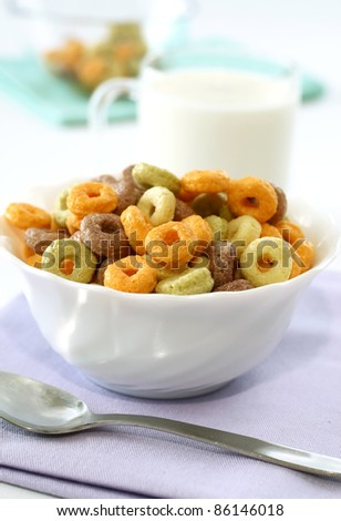 colorful muesli in bowl and milk in glass on white