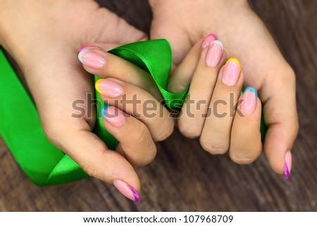 Colorful nails and green ribbon