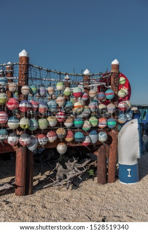 Colorful nautical round fishing net floats with nets, ropes, wood pilings, boat vent and blue sky