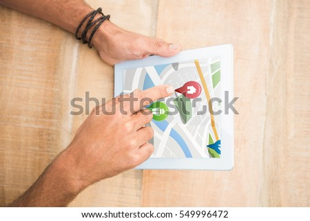Colorful navigation pointers with various representations on map against hand pointing blank screen tablet Digital image of colorful navigation pointers with various representations on map #549996472