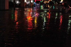 Colorful neon light reflections on cobblestone street scene in Paris.  Dark and rainy evening in city. Horizontal photo with copy space.