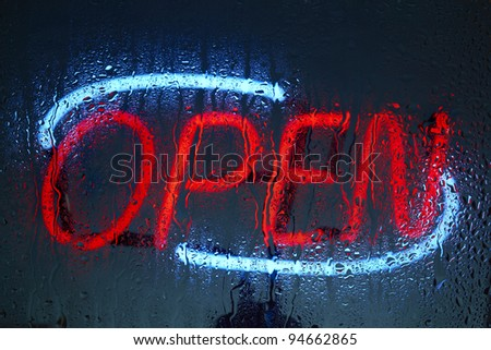 Colorful neon open sign seen through a rainy night