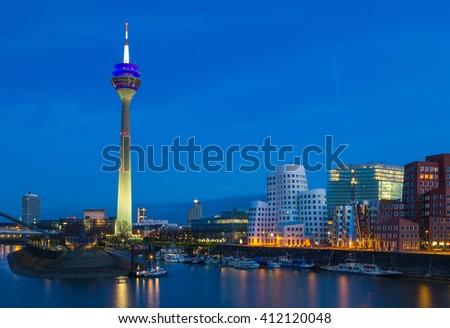 Colorful night scene of Rhein river at night in Dusseldorf. Rheinturm tower in the soft night light, Nordrhein-Westfalen, Germany, Europe. #412120048