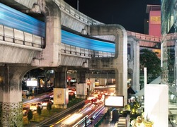 Colorful night street with skytrain and traffic jam in Bangkok