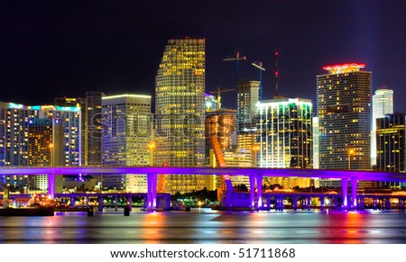 Colorful night view of city of Miami Florida with downtown buildings in the financial business district and Biscayne bridge bridge