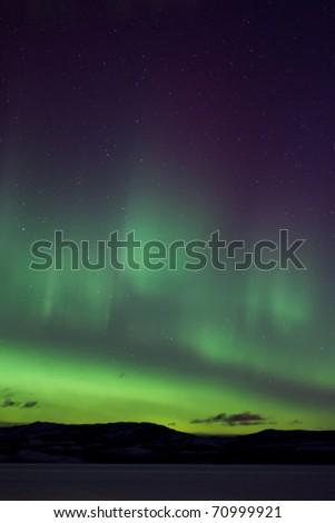 Colorful northern lights (aurora borealis) substorm on dark night sky with myriads of stars. - stock photo