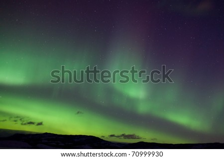 Colorful northern lights (aurora borealis) substorm on dark night sky with myriads of stars.