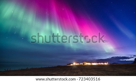 colorful northern lights in a iceland landscape with cottage mountain and sea #723403516