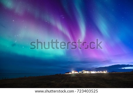 colorful northern lights in a iceland landscape with cottage mountain and sea