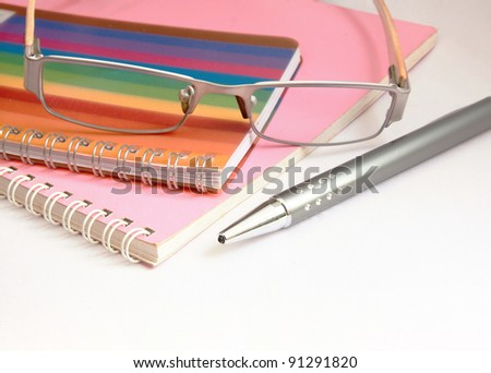 Colorful notebook pen and glasses